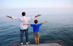 Father and young boy with arms stretched upwards